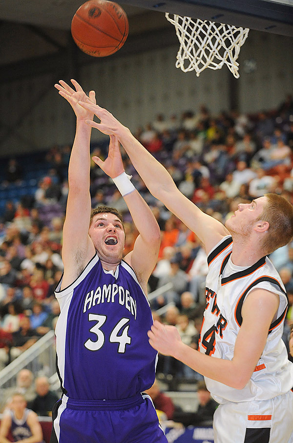 Hampden Academy's Noah Burditt (left) goes up for a shot over Brewer's Nate Carson during the first half of the Class A semifinal game in Augusta Wednesday.