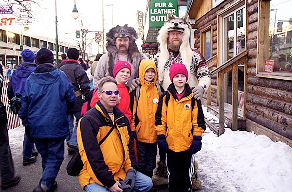 Brooksville parent chaperone Russell Osborn (front left) and Brooksville students (Damon Gray, Wesley Moores, and Aaron Osborn (Center-left to right) stand in front of two Alaskan Iditarod fans. In March 2005, students from Brooksville, Maine traveled to Alaska to observe the famous Iditarod dog sled race. PHOTO COURTESY OF NADA LEPER