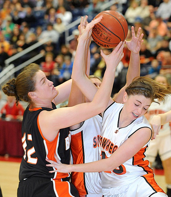 Skowhegan's Adrienne Davis (right) and Jaimi Poland battle for a rebound with  Brunswick's Lydia Caputi during the second half of the Eastern Maine Chamionship game at the Augusta Civic Center Friday. Liz Noddin scored with less then 5 seconds left on the clock earning Skowhegan the 38-36 victory.