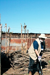figure 1:  Greg Campbell of Jonesport starts construction of a new house. In the background is the remnants of the corn stalk house that the Guatamalen family of five previously shared.  PHOTO BY LARRY FINNEGAN