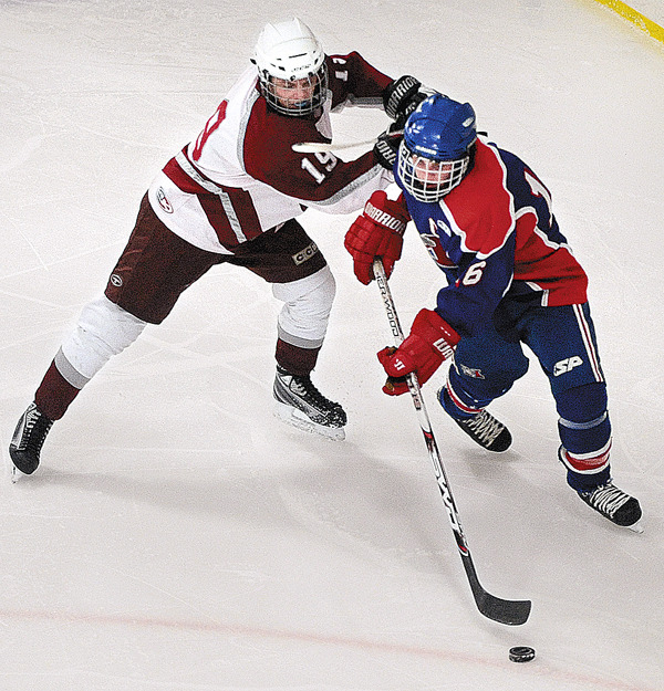 Bangor's Jacob Turmel (left) battles for the puck with Messolonskee's Nate Nadeau during the second period of the class A quarter-final game in Bangor Tuesday evening. (Bangor daily News/Gabor Degre)