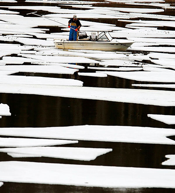 In this photo taken on Tuesday, Feb. 23, 2010, a clammer rakes for quahogs in the New Meadows Lake in Brunswick, Maine. Scientists are sounding a warning that the New England shellfish industry faces a potential threat of widespread red tide outbreaks this spring and summer.Researchers say indicators are in place suggesting a significant regional bloom of the toxic algae that causes red tide. (AP Photo/Pat Wellenbach)