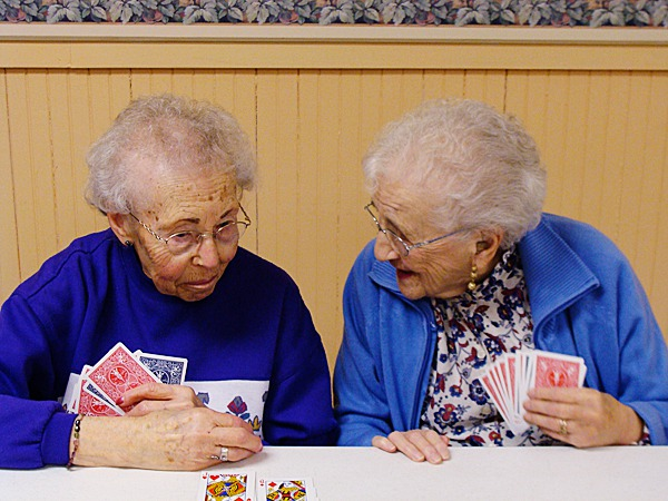 Gerry Comeau, 85, of Milo, (right), chats with Natalie Harris, 92, of Milo, as the pair wait their turn at the card game of ''Hand and Foot'' being played Wednesday, at the Warming Center in the Park Street Methodist Church in Milo. The center brings senior citizens together for camaraderie and a hot meal. BANGOR DAILY NEWS PHOTO BY DIANA BOWLEY
