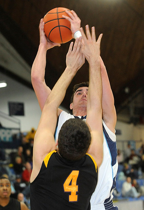 The University of Maine's Troy Barnies goes up for a shot over Albany's  Fran Urli (4) during the first half of the game in Orono Wednesday evening. BANGOR DAILY NEWS PHOTO BY GABOR DEGRE