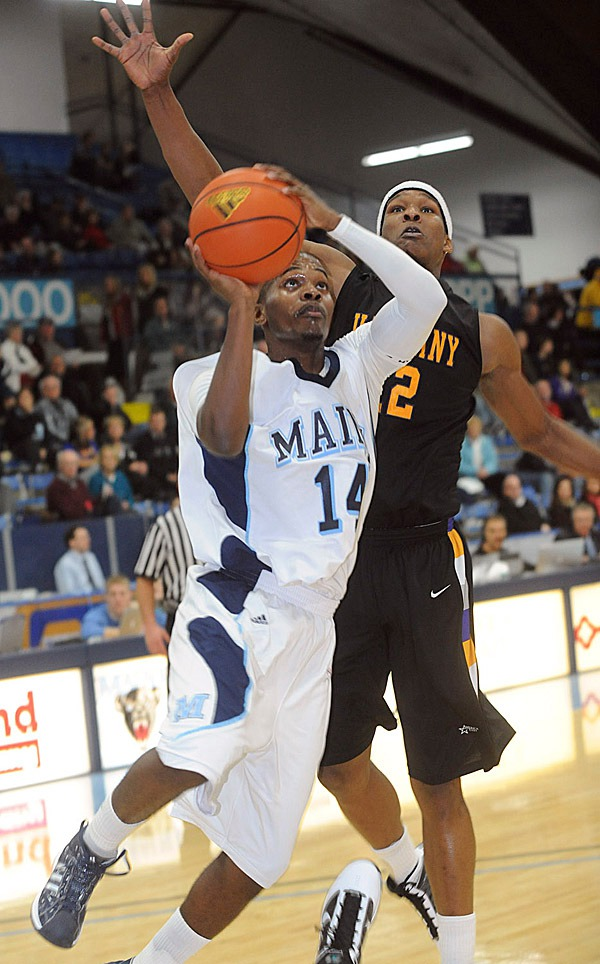 The University of Maine's Terrance Mitchell (14) drives for the basket past Albany's  Scotty McRae during the first half of the game in Orono Wednesday evening.