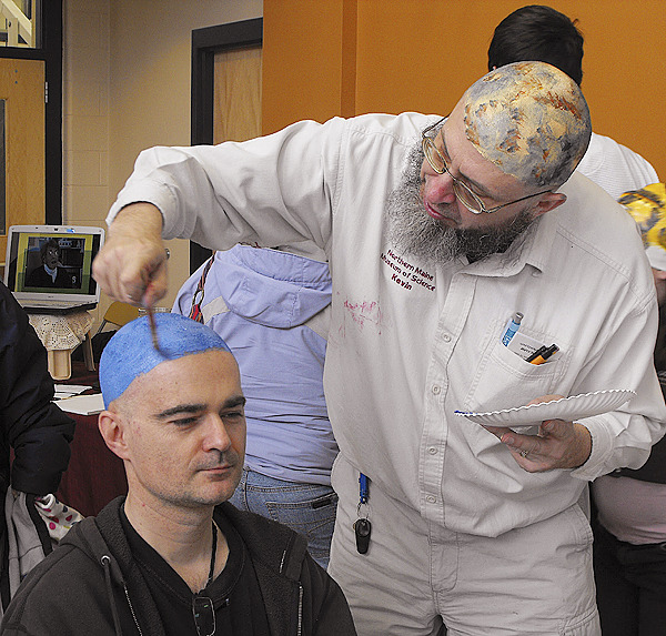 Tomasz Herzog, left, of Presque Isle, has his head painted to resemble Neptune by Kevin McCartney, one of the organizers of Planet Head Day at the University of Maine at Presque Isle. The fourth annual Planet Head Day was held on Saturday to increase awareness of NASA's mission to Pluto and to garner money for the nonprofit Caring Area Neighbors for Cancer Education and Recovery (C.A.N.C.E.R,) , which provides support to families and individuals dealing with cancer. As part of the event, participants donned theatrical bald caps or had their hair shaved off and then had their heads painted to look like planets, moons, asteroids and comets. BANGOR DAILY NEWS PHOTO BY JEN LYNDS