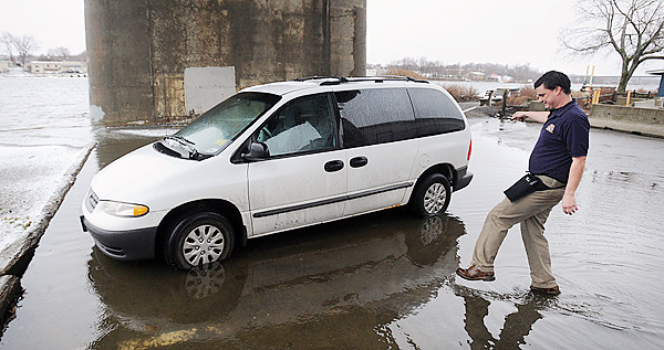 Kyle Grey, a waiter at the Sea Dog restaurant in Bangor, walks through water to get to his car which was surrounded by high tide floodwater from the Penobscot River under the Joshua Chamberlain Bridge in Bangor Monday, March 1, 2010.  &quotOne of the the guys came around and warned us that the river was flooding the parking lot.  It's not the worst I have seen it but I'm glad I got out here to move my car before the water got higher,&quot Grey said. (Bangor Daily News/Gabor Degre)
