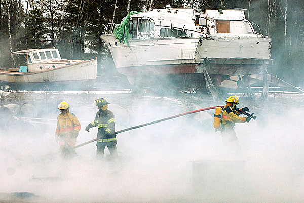 Steuben firefighters hose down the remains of a building at RP Boat Shop on Route 1 in Steuben on Monday morning, March 1, 2010 after an explosion and subsequent fire leveled the structure. No one was harmed or in the building, which was used to house boat molds, when the fire began. (Bangor Daily News/Bridget Brown)