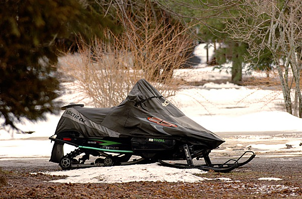 A snowmobile sits on a small patch of snow along Ohio Street in Glenburn on Monday, March 1, 2010. BANGOR DAILY NEWS PHOTO BY KEVIN BENNETT