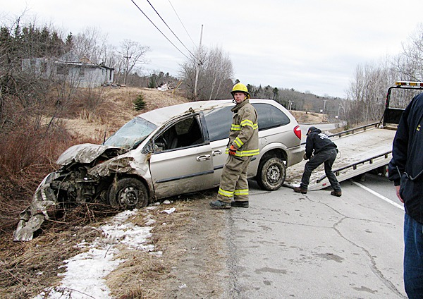 SEARSPORT - A rescue worker helps load a totaled van onto a wrecker truck Tuesday morning on U.S. Route 1. BANGOR DAILY NEWS PHOTO ABIGAIL CURTIS