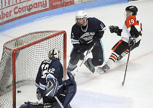 Presque Isle's goalie Josh MacFarline (left) can't make the save on a shot by  Brewer's Kyle Alexander (right) during the second period of the Eastern Maine Class B final game at the Alfond Arena in Orono Tuesday evening.  Alexander scored Brewer's second goal of the game.  at center is Presque Isle's Jason Martin