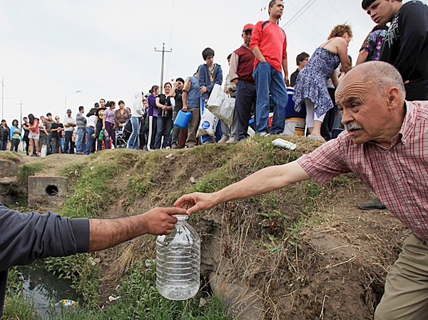 A man receives an empty bottle to fill it with water from a damaged main in Concepcion, Chile, Tuesday, March 2, 2010. Central Chile was hit by a powerful earthquake Feb. 27. (AP Photo/Ricardo Mazalan)