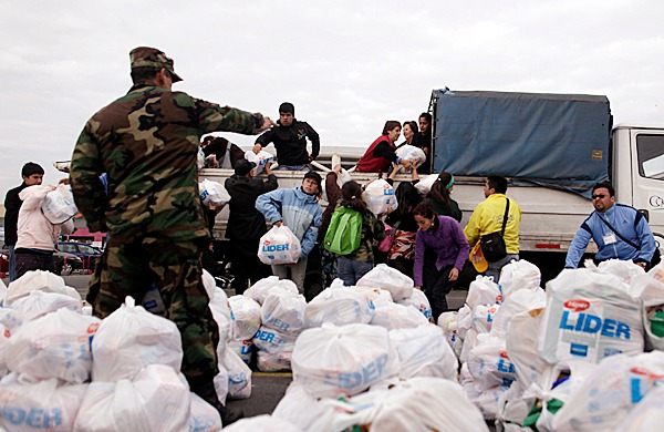 Volunteers load bags containing supplies on a vehicle  to be distribute among earthquake victims in Concepcion , Chile, Wednesday, March 3, 2010. An 8.8-magnitude earthquake struck central Chile early Saturday. (AP Photo/Natacha Pisarenko)