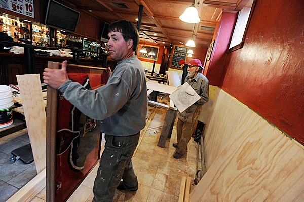 Jim Bence,foreground, new owner of the Bear Brew Pub in Orono, removes sports memorabilia to work on the walls  as  contractor John Mansfield of Bangor works behind him Wednesday afternoon, March 3, 2010. Bence said he hopes to re-open the pub and pizza oven in a few weeks with more renovations to come. BANGOR DIALY NEWS PHOTO BY JOHN CLARKE RUSS