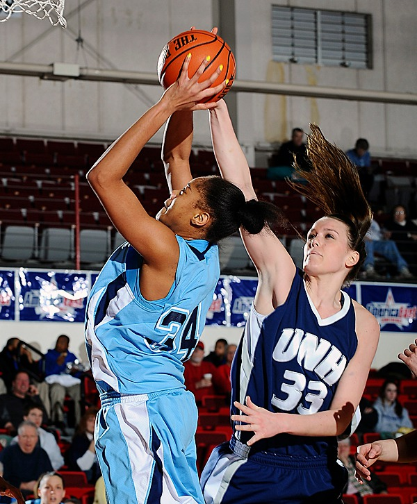 Corinne Wellington of Maine has her shot blocked by UHN's Jill McDonald. PHOTO BY STEVE MCLAUGHLIN