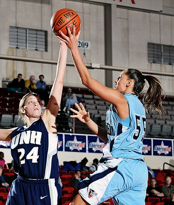 Maine's #55 Katia Bratishko drives for a layup against UHN 's #24 Chrissy Hall.  UNH advanced to the second round of the America East Women's Basketball Tournament.  PHOTO BY STEVE MCLAUGHLIN