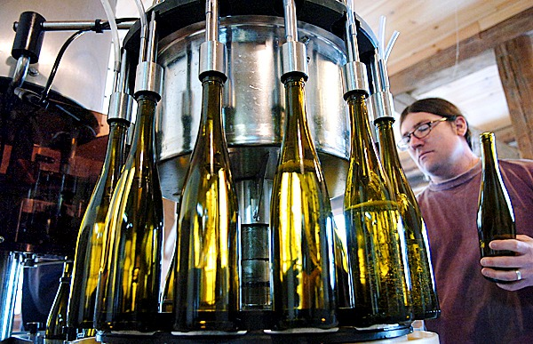 Brian Smith bottles a Riesling at the Cellardoor Winery in Lincolnville on Thursday, March 4, 2010. The winery, which offers 14 varieties, recently had business expansion plans approved to build a new 9,000 square foot building across from the more than 200-year-old barn they are currently producing out of on Youngtown Road. The expansion will boost production from 6,000 cases in 2009 to more than 9,000 cases a year.  BANGOR DAILY NEWS PHOTO BY BRIDGET BROWN