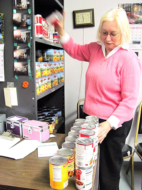 Kathy Kehoe's father, Earl Dean, was the director of the Pittsfield Area Food Pantry for 26 years before he died on Feb. 22. Kehoe, shown above stocking a shelf at the pantry, has assumed her father's legacy of running the pantry.  BANGOR DAILY NEWS PHOTO BY CHRISTOPHER COUSINS