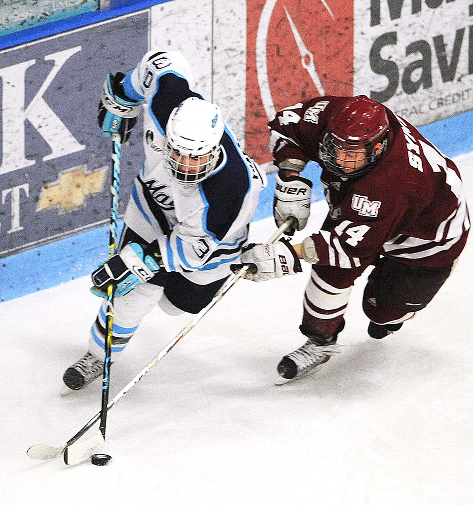 The University of Maine's Joey Diamond (left) battles for the puck with T.J. Syner of the University of Massachusets during the first period of the game at the Alfond arena in Orono Friday.  BANGOR DAILY NEWS PHOTO BY GABOR DEGRE