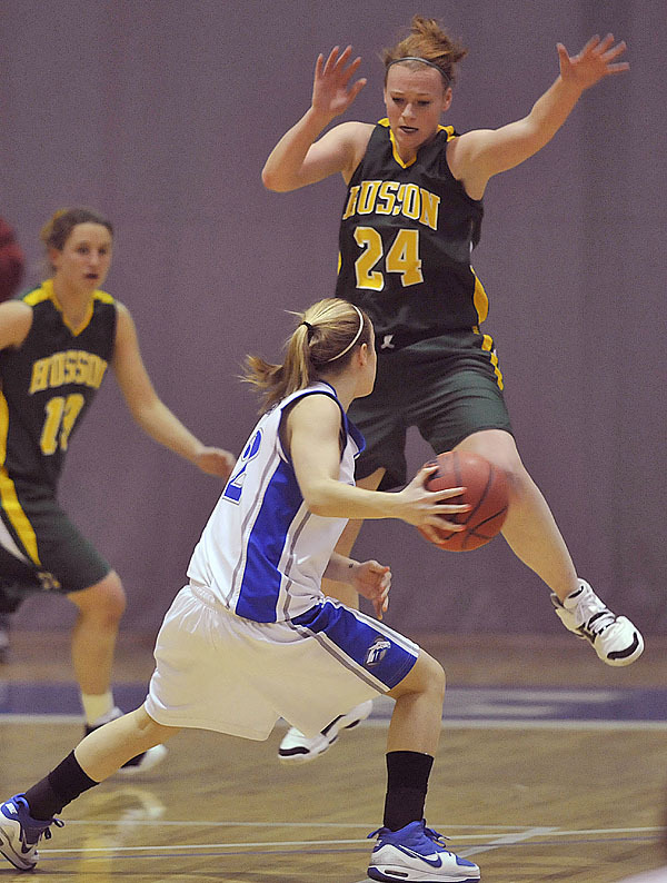 Husson's Lindsey Barnes, (24), gets some  air blocking the drive of Colby's Diana Manducca, (12),  in the first half of their playoff game at Colby College, Friday, March 5, 2010.Bangor Daily News/Michael C. York