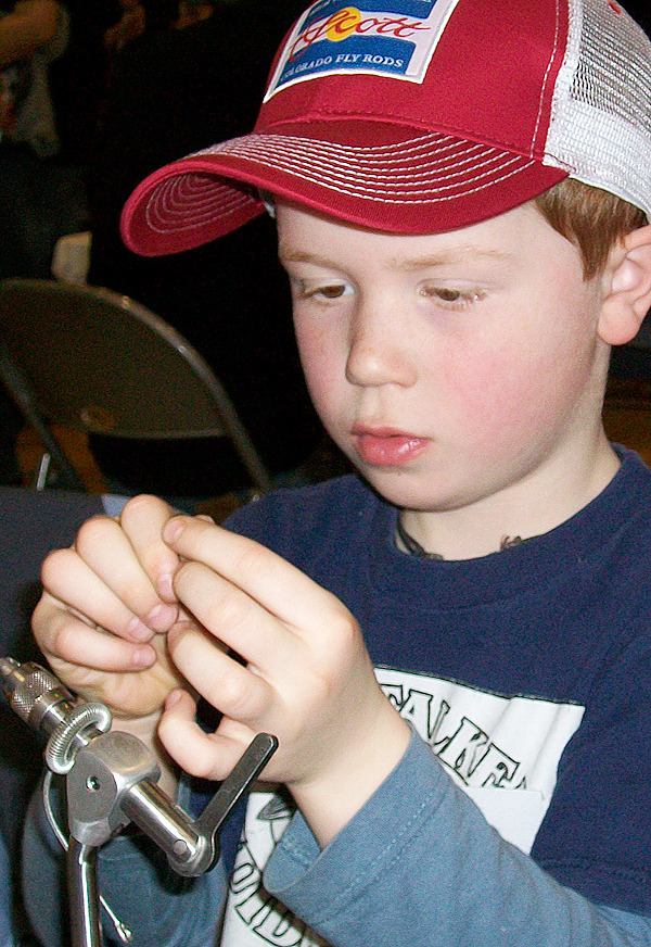 Jax McKay,7, of Winterport ties a fly at the Cabin Fever Reliever Outdoor Show in Brewer Sunday, Feb. 28, 2010. (Bangor Daily News/John Holyoke)