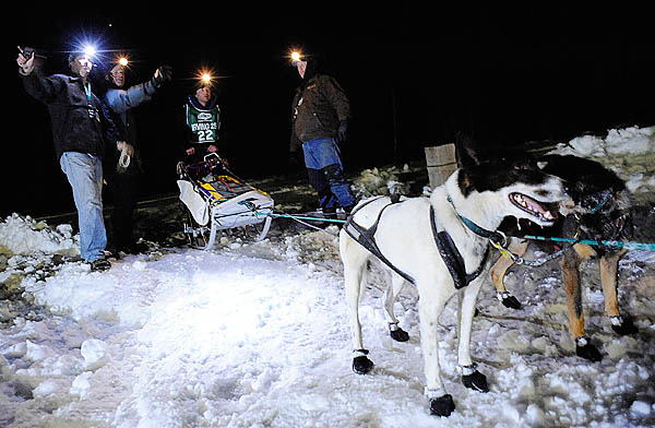 Tallking with Can-Am volunteers, musher Rene Marchildon (#22), a competitor in the Can-Am 250,  gets directions to a resting spot for his dogs after arriving at the Rocky Brook camp checkpoint early Sunday morning, March 7, 2010. By late Saturday, Marchildon was proving himself to be a top contender in this year's race. (Bangor Daily News/John Clarke Russ)