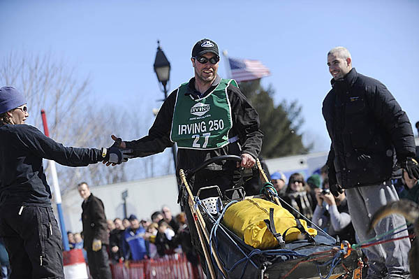 Adam Cummings of White River Junction, Vermont gets encouragement from the the sidelines as his dog team carries him down Main Street during the start of the Can-Am Crown 250 in downtown Saturday, March 6, 2010.  (Bangor Daily News/John Clarke Russ)