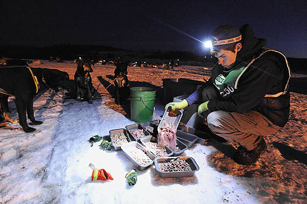 Musher Jacob Golton, 18, of L'Amable, Ontario prepare meals for his dog team during their mandatory layover at the Portage Lake checkpoint in Portage Lake, Maine shortly after sundown Saturday, March 6, 2010. (Bangor Daily News/John Clarke Russ)