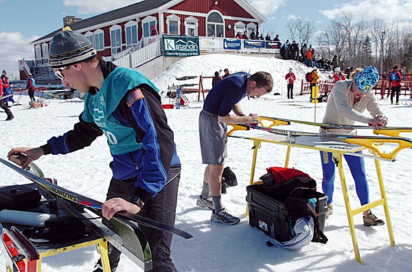 Skiing coaches from Alaska including (from left) Nick Crawford, Nate Normandin and D'Anna Gibson wax skis for their athletes at the 2010 XC Junior Olympics at the Nordic Heritage Center in Presque Isle on Monday, March 8, 2010. Normandin took advantage of Monday's mild weather to work on his tan. BANGOR DAILY NEWS PHOTO BY BRIDGET BROWN