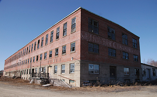 The first extensive site-clearing work began this week at the former tannery building in Howland, but the main building will stay erect at least for another year, as town officials look for federal or state grant funds that will pay for the building's demolition. BANGOR DAILY NEWS PHOTO BY NICK SAMBIDES JR.