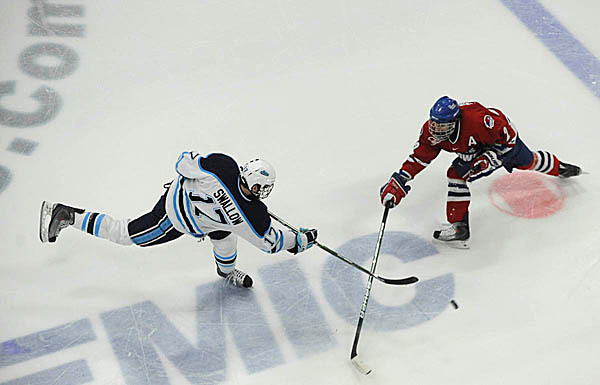 U Maine's Kevin Swallow, left, moves the puck past U Mass-Lowell's Jeremy Dehner in the first period of U Maine's third Hockey East quarterfinal series game with U Mass -Lowell at Alfond Arena Sunday night, March 14, 2010. (Bangor Daily News/John Clarke Russ)