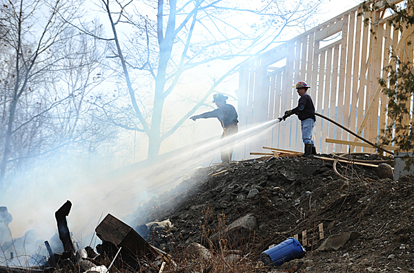 Firefighters from Hermon and Levant hose down a pile of stumps behind 600 Newburgh Road on Monday, March, 15, 2010. Maine Forest Ranger Jerry Parsons says the fire is under investigation. BANGOR DAILY NEWS PHOTO BY KEVIN BENNETT