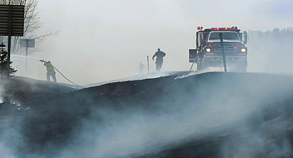 Fire crews scramble to extinguish flames along the northbound lane of interstate 95 in Newburgh on Monday, Feb, 15, 2010. Traffic along the north bound lane was stopped for 20 minutes while firefighters from Hermon, Carmel and Newburgh brought the grass fire under control. Officials are warning that warmer temperatures combined with high winds are creating a fire danger earlier this year due to a lack of snow cover. BANGOR DAILY NEWS PHOTO BY KEVIN BENNETT
