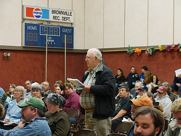 More than 100 Brownville residents listened Monday as resident John Owens moved to cut the administration account during the annual town  meeting. Residents ultimately voted to slash the account by 10 percent. BANGOR DAILY NEWS PHOTO BY DIANA BOWLEY