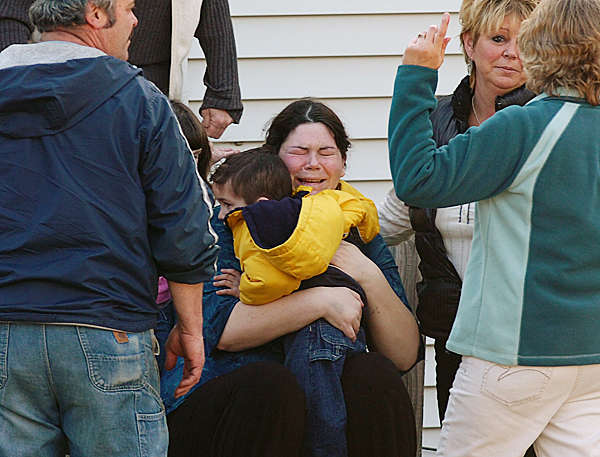 Logan Knight, 3, is embraced by his mother Nicole Dammier as she is comforted by family and friends at their Mud Creek Road home in Lamoine on Wednesday, March 17, 2010. The boy wandered off with his dog but was found by a neighbor in the woods about 800 yards from his home. BANGOR DAILY NEWS PHOTO BY BRIDGET BROWN