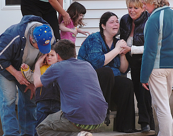 Logan Knight, 3, (lower left) is surrounded by family members after he was found in the woods near his home as his mother Nicole Dammier (third from right) is comforted by family and friends at their Mud Creek Road home in Lamoine on Wednesday, March 17, 2010. The boy was found by a neighbor safe, but scared, in the woods about 800 yards from his home after he wandered off with his dog. BANGOR DAILY NEWS PHOTO BY BRIDGET BROWN