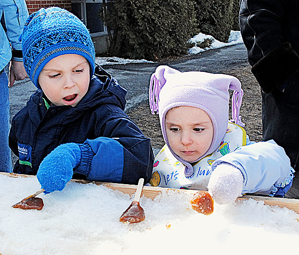 It was a sweet taste of culture for Gavin Voisine, 5, and his sister Ella, 3, during the annual Sucrerie at the University of Maine at Fort Kent. Their mother Hannah Voisine said she brought the two for the event from Frenchville to expose them to a part of their Acadian heritage. BANGOR DAILY NEWS PHOTO BY JULIA BAYLY