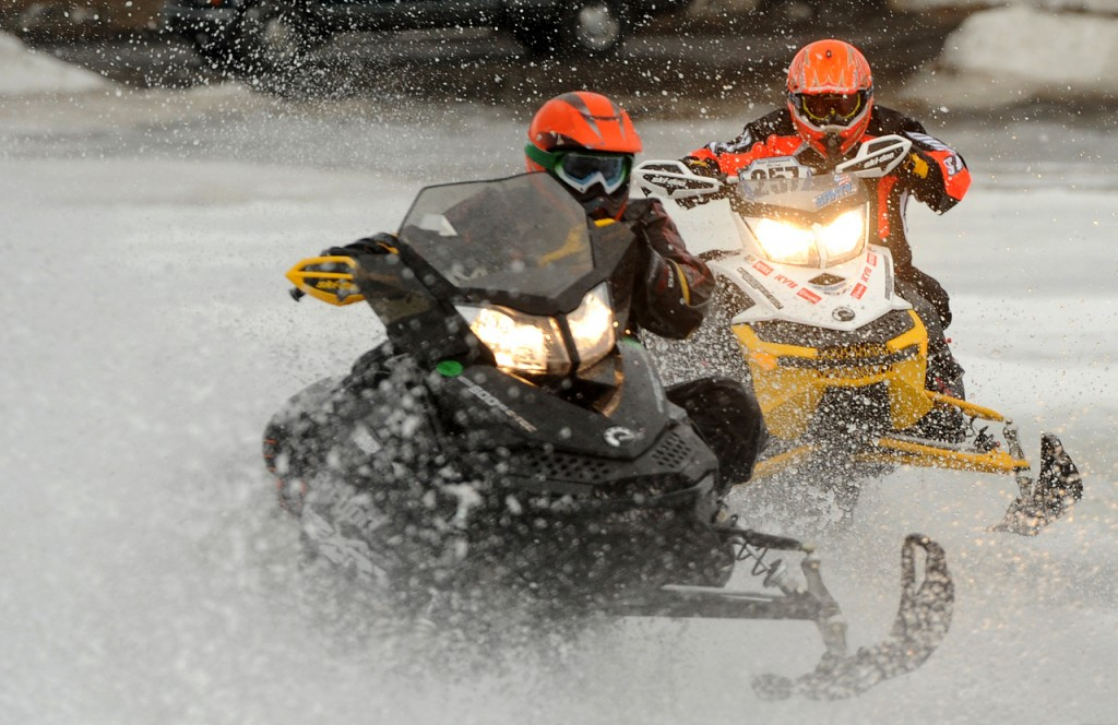 Ryan Scripture (left) of Carmel battles for position in a turn with Joel Santy of Malone, N.Y., during the feature race of the first annual Maine Pro-Am 100 snowmobile racing event on the ice of Moosehead Lake in Greenville on Saturday. Scripture won in the semi-pro 600 category in the 48-mile-long race. Race organizers said that the event was going to be held at Little Moose Mountain but they had to move the race onto the ice of Moosehead Lake because of the unusually mild weather and the snow conditions. Buy Photo