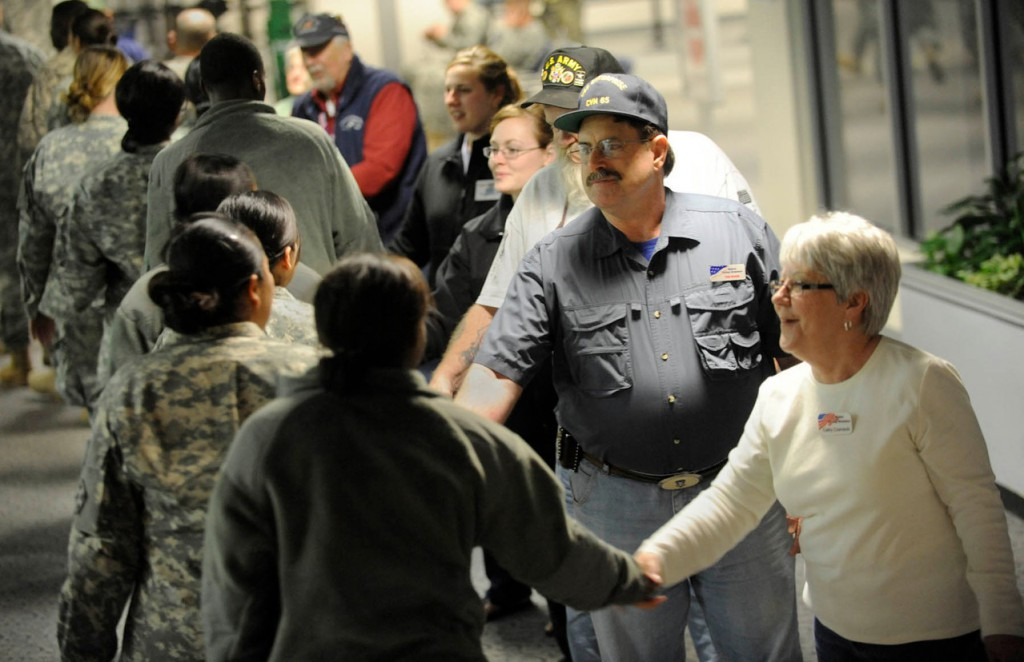 The Maine Troop Greeters at Bangor International Airport welcome troops from Fort Carson, Colo. after their flight arrived shortly before 1 a.m. Monday, March 22, 2010. Among the Maine Troop Greeters (from right to left) were Cathy Czarnecki of Hermon, Tom Ruane of Hermon, Darrell McTigue (partially obscured) of Dedham, Brianna Hanington (University of Maine freshman and ROTC) of Bancroft, ME, Paige Montgomery (University of Maine freshman and ROTC) of Brunswick,ME and Louis Horvath of Holden. The Monday morning flight  carrying 279 troops included  the 1 millionth soldier to come through Bangor since May 2003. (Bangor Daily News/John Clarke Russ)