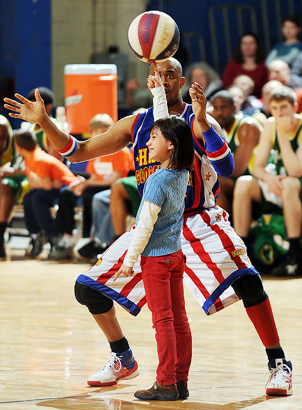 Harlem Globetrotter Scooter Christensen watches as he gets a young fan to spin the ball on her finger on Monday, March 22, 2010 at the Bangor Auditorium during play against the Washington Generals. (Bangor Daily News/Kevin Bennett)