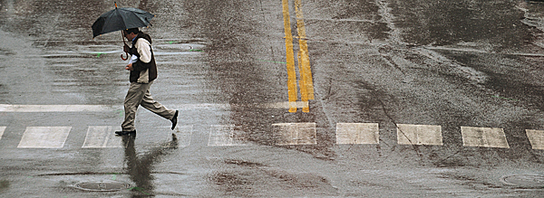 A pedestrian dashes across Franklin Street during a downpour in Bangor on Tuesday, March 23, 2010. According to the National Weather Service in Carbiou, heavy rains may produce minor flooding through Wednesday with a  total of 2 to 3 inches rainfall. BANGOR DAILY NEWS PHOTO BY KEVIN BENNETT