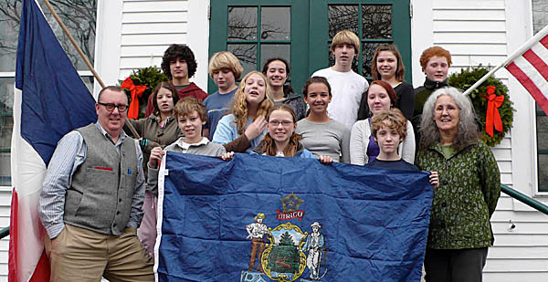 Seventh and eighth grade students from the Adams School in Castine, pose with flags from Maine, American and France as they  make last minute preparations for a one-week trip to France to visit their sister school in the town of St. Castin. The trip is part of an ongoing exchange with the school and the town which is the birthplace of the Baron de Castin, for whom the Maine town was named. (Photo courtesy of the Adams School)