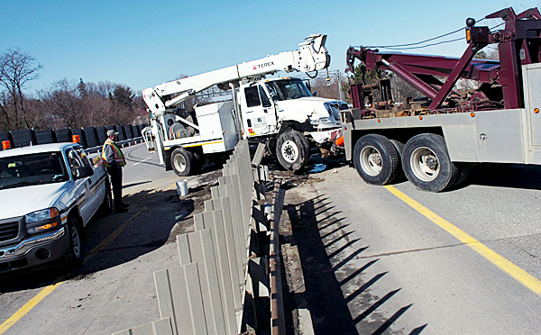 Bangor Hydro Electric Company workers and a tow truck driver work to remove a utility truck which crashed through a guardrail on I-95 near the Broadway exit in Bangor on Thursday morning, March 25, 2010. One person suffered a laceration in the accident which happened around 8 a.m. and tied up traffic for several hours. (Bangor Daily News/Bridget Brown)