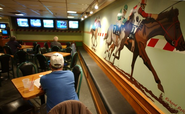 Patrons at Miller's off track betting facility at Miller's Restaurant in Bangor watch horse races Thursday on a bank of televisons. Miller's has announced it will close the Main street restaurant in May, and Penn National will convert the property into a temporary racino. (BANGOR DAILY NEWS PHOTO BY KEVIN BENNETT)