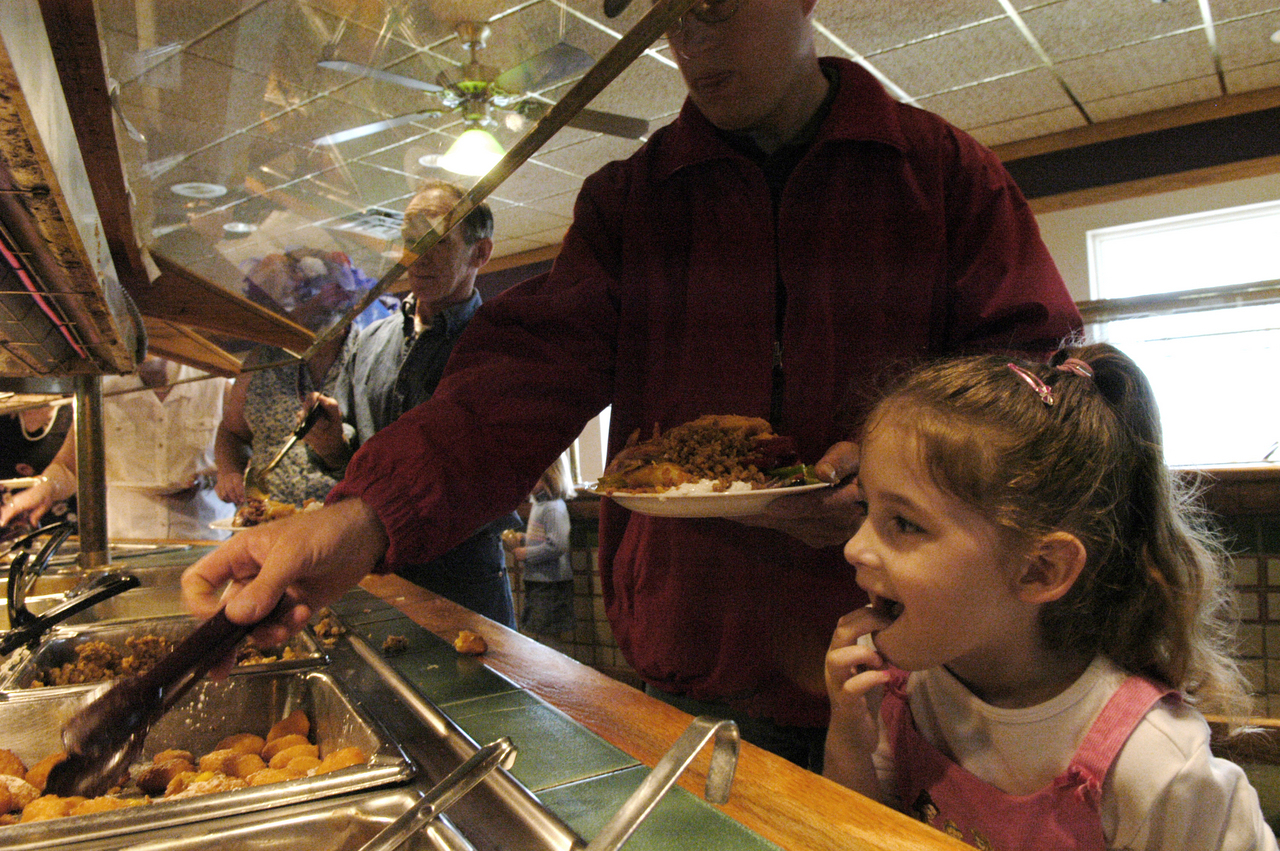 Natalie Rickards, 5, of Crystal, checks out the buffet at Miller's Restaurant as her father, Albert Rickards, loads his plate during the family's Mother's Day outing on Sunday. The Rickards family periodically comes from Aroostook County to dine there.  (BANGOR DAILY NEWS PHOTO BY JOHN CLARKE RUSS)