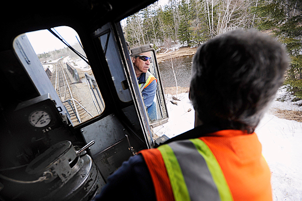 Engineer Rick Cameron of the Montreal, Maine and Atlantic railway looks at his rearview window as he reverses Engine 100 at the Squapan station in Masardis Thurdsday, March 18, 2010. Engine 100 was built in 1957.  Safety concerns and poor maintenance along sections of the MM&A railway in northern Maine limit the speed of their freight trains where 10 to 15 mph is common.  State officials are seeking a $25 million bond to repair rail in Aroostook, Penobscot and Androscoggin counties. Without such aid railways like MM&A might have to abandon their 241 miles of track which remain crucial to Maine industries.  BANGOR DAILY NEWS PHOTO BY JOHN CLARKE RUSS