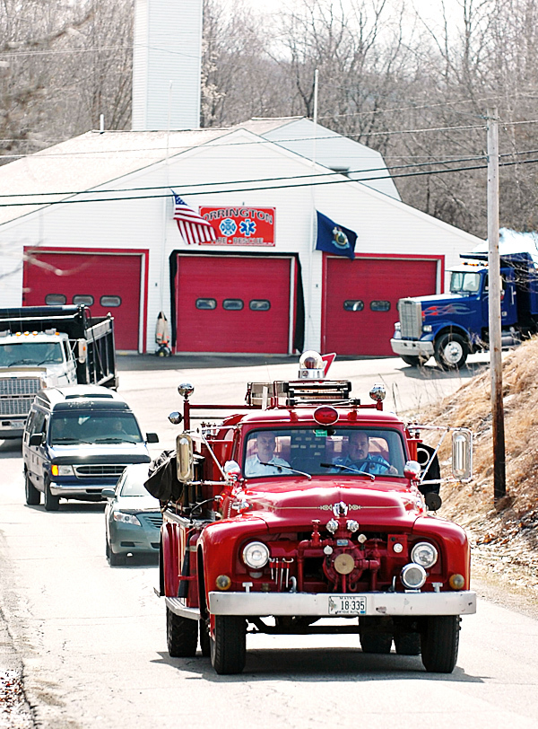 Orrington Fire Chief Mike Spencer (left in firetruck) and Lt. Mark Kenney (right) lead a procession in Engine 2 escorting the remains and fire helmet of Leslie &quotLes&quot Grover from the East Orrington Congregational Church to Marston Cemetery in Orrington on Friday morning, March 26, 2010. Les was remembered for his long-time service to the community including 41 years at the fire department. BANGOR DAILY NEWS PHOTO BY BRIDGET BROWN