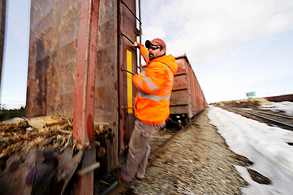 Montreal, Maine and Atlantic railway conductor Jarrad Clark (cq) hangs on the back car as engineer Rick Cameron (not pictured) backs up the train at Skerry Siding in Portage to link up more rail cars Thursday, March 18, 2010. Safety concerns and poor maintenance along sections of the MM&A railway in northern Maine limit the speed of their freight trains where 10 to 15 mph is common.  State officials are seeking a $25 million bond to repair rail in Aroostook, Penobscot and Androscoggin counties. Without such aid railways like MM&A might have to abandon their 241 miles of track which remain crucial to Maine industries. BANGOR DAILY NEWS PHOTO BY JOHN CLARKE RUSS