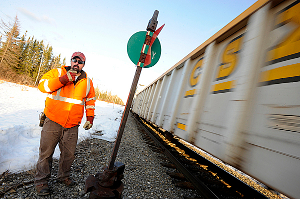 Just before sunset, conductor Jarrad Clark radios back to engineer Rick Cameron as Cameron rolls the train past Clark and a rail switch on the Montreal, Maine and Atlantic railway on the train's return to Squapan Station from Presque Isle Thursday, March 18, 2010.  BANGOR DAILY NEWS PHOTO BY JOHN CLARKE RUSS
