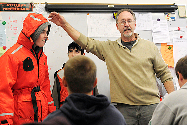 Deer Isle-Stonington High School marine trades instructor Tom Duym (cq) has student freshman Josh Gove,15 of Deer Isle try on a flotation jacket as freshman Tyler Wheaton (in background) 15, of Stonington and other students look on in class Friday morning, March 26, 2010. The Maine Dept. of Education recently released a list of the 10 &quotpersistently lowest achieving schools,&quot Schools on the list which includes Deer Isle-Stonington High School, are eligible for a total of $12 million in federal improvement grants if they take certain steps. BANGOR DAILY NEWS PHOTO BY JOHN CLARKE RUSS